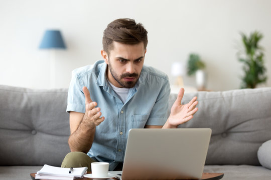 Mad stressed young man angry about stuck laptop data loss