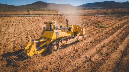 Aerial image of a bulldozer pushing and ripping ground on an agricultural piece of land