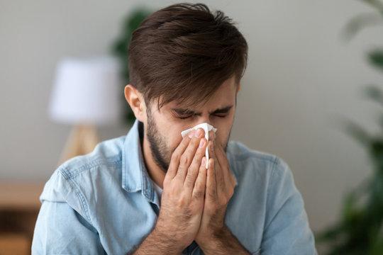 Sick man got flu allergy sneezing in handkerchief blowing nose