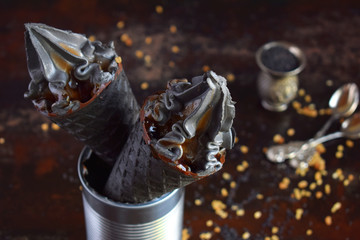 Black ice cream with sesame and caramel in black waffle ice cream cones. Copy space. Trendy summer food