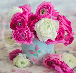 Floral composition with a pink and white Ranunculus flowers.