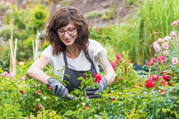 Gärtnerin schneidet lächelnd die Rosenpflanzen im Gartencenter