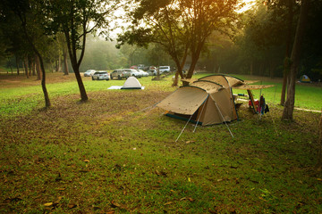 nature landscape camping tent with tree on green grass meadow in jungle for trekking picnic on holiday relax and vacation travel on autumn winter or summer with warm sunlight at Ban Krang Camp