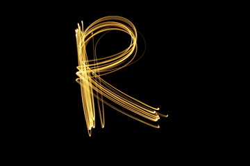 Long exposure, light painting photography.  Letter r in a vibrant neon metallic yellow gold colour against a black background.  Alphabet series.