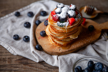 Pancakes with berries and maple syrup and sugar powder