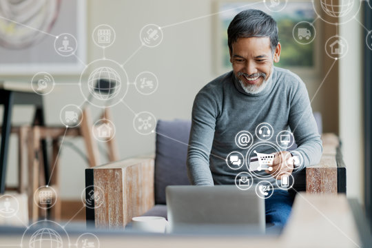 Asian or Hispanic man using Laptop and credit card payment shopping online with icon customer network connection on screen and connecting with omni channel system. Older man satisfied with CRM system