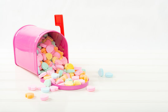 Pink mailbox full of candy conversation hearts on a white bead board table with a shallow depth of field and copy space