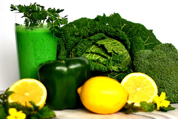 Savoy cabbage, kale, broccoli, paprika, sliced lemon, glass of healthy green raw vegan smoothie ,decorated with parsley arranged on the white background.