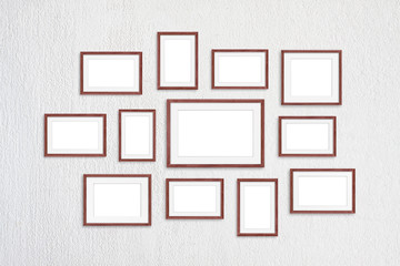 Blank frames collage, twelve brown realistic wooden frameworks isolated on white plastered wall