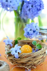 Orange easter egg in nest and blue flowers.