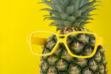 Closeup of a pineapple wearing a pair of yellow eyeglasses isolated on yellow background