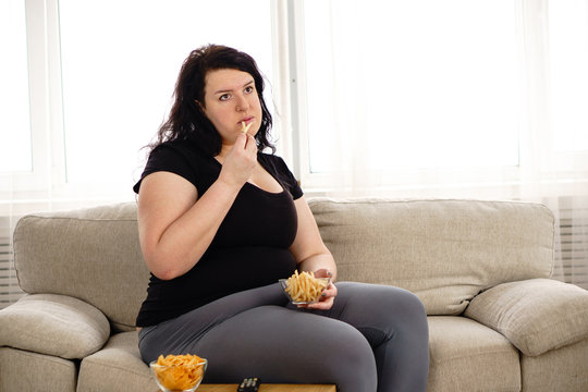 lack of physical activity, imbalanced nutrition, laziness, homebody. lonely fat woman watching series at tv eats junk food