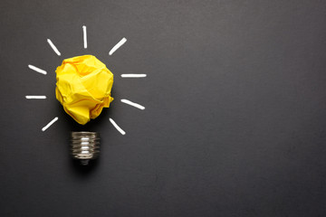 Great idea concept with crumpled yellow paper light bulb isolated on dark background