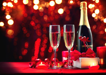 Valentine's Day romantic dinner. Champagne, candles and gift box over holiday red background. Wedding celebrating. Birthday party