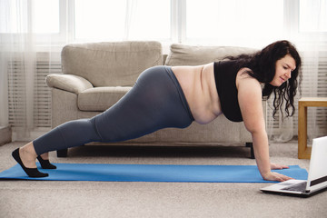 online fitness class, home training, technology and diet. overweight woman doing plank under the...