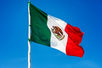 Mexican national flag of Mexico flapping in the wind against a beautiful blue sky in the caribbean on the coast of the Riviera Maya in South America.