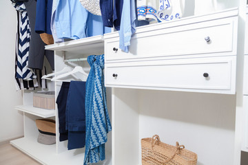 beach blue clothes and windsurf suit hanging in white wardrobe at home