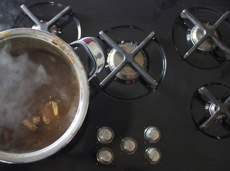 Steam rising from boiling pot. Metal Pot on black stove in modern kitchen