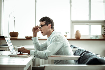 Serious male person staring at screen of his laptop