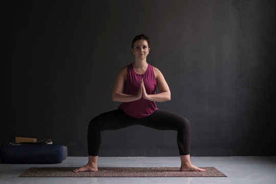 Beautiful young yoga model working out indoor doing Goddess or Sumo Squat Pose