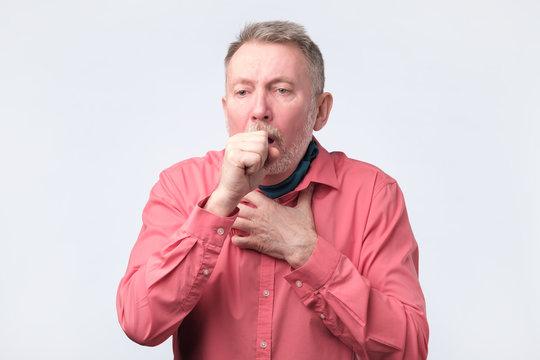 European gentleman in red shirt coughing because of pulmonary diseas