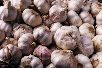 Vitamin healthy food spice image. Spicy cooking ingredient picture. White garlic pile texture. Fresh garlic market table closeup photo. Pile white garlic head heap top view.