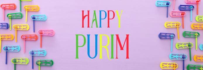 top view image of Purim celebration concept (jewish carnival holiday) over purple background. Top view, flat lay.