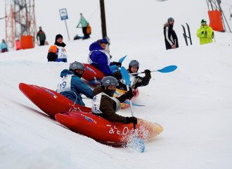 People compete during a downhill snow kayak event in Kuutsemae