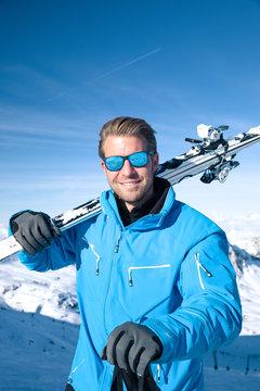 Junger sportlicher Mann fährt Ski, macht Winter Sport in einem Winter Paradis. Schnee bedeckte Berge, blauer Himmel und Farbenfroher Ski Anzug
