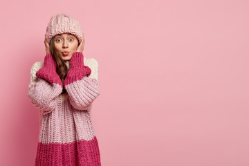 Studio portrait of young lovely woman has folded lips, makes grimace at camera wears knitted hat and loose pink jumper, isolated over rosy background with empty space for your promotion or slogan