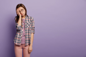 Studio shot of sad lonely woman keeps hand on cheek, dressed in checkered shirt and trousers, poses over purple background, focused upwards in displeasure, being deep in thoughts. Copy space