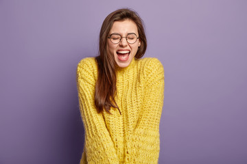 Overjoyed happy young European woman feels overemotive, opens mouth, dressed in yellow loose knitted sweater, feels impressed by good news, isolated over purple background. Good emotions concept