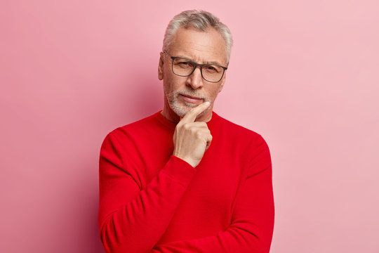 Headshot of handsome grey haired man holds chin, dressed in red sweater, looks directly at camera, has thoughtful expression, poses over rosy background. Pensive grandfather has attentive gaze