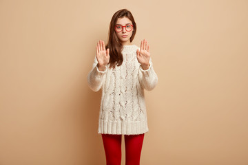 People and prohibition concept. Serious woman extends arm in stop gesture, forbides something, shows palms, wears optical glasses, red sweater and red tights, isolated over brown background.