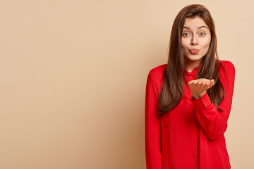 Studio shot of good looking woman keeps lips folded, sends air kiss, stretches hand, wears red shirt, poses over beige background with copy space for your promotional content or advertisement