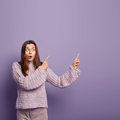 Vertical shot of surprised puzzled brunette young female model points upwards, has shocked expression, demonstrates copy space, wears knitted oversized jumper, isolated on purple background.