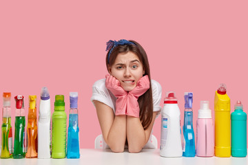 Image of frustrated Caucasian woman holds chin, has puzzled facial expression, wears headband and casual t shirt, sits at workplace, uses different detergents, isolated over pink background.