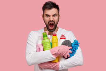 Photo of dissatisfied unshaven man holds bottle of cleaning products, holds sponge, dressed in casual clothes, exclaims in dissatisfaction, isolated over pink background. Hard working human indoor