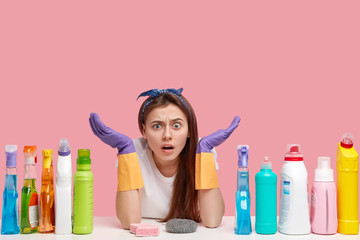 Isolated shot of puzzled hesitant young woman spreads palms, has displeased expression, wears stylish headband, uses cleaning detergents, isolated over pink background with empty space above