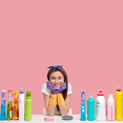 Positive smiling woman busy with house work, holds chin, wears protective gloves, looks directly at camera, uses cleaning detergents, isolated over pink background, empty space for your text