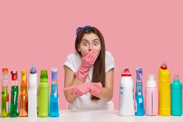 Photo of scared busy young woman covers mouth, looks in bewilderment, points at bottles of cleaning detergents, wears casual t shirt and headband, isolated over pink background, does house work