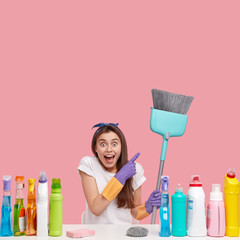 Vertical shotof pleased merry young housewife points at broom with satisfaction, wears protective gloves and t shirt, uses cleaning products, isolated over pink background. Housecleaning concept
