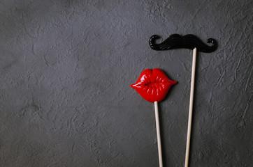 Photo booth props mustache lips on dark stone board background.