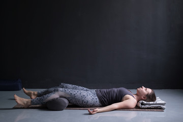 woman working out, doing yoga exercise on wooden floor, lying in Shavasana