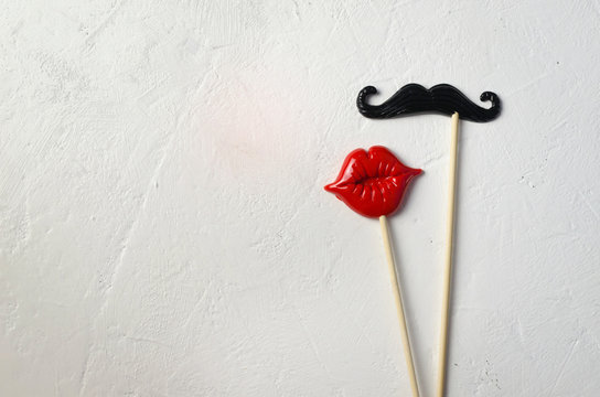 Photo booth props mustache lips on white stone board background.