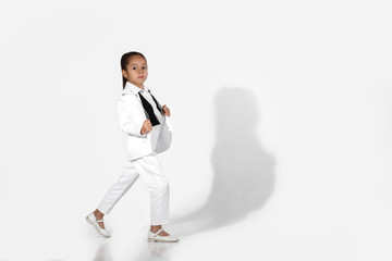 fashion beautiful little girl model in a white suit and untied bow tie on white background. fashion child concept