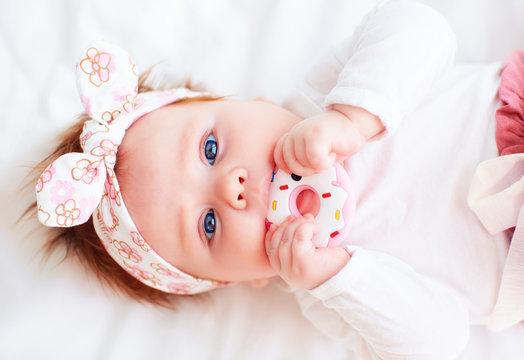 cute little baby girl nibble a silicone doughnut teether