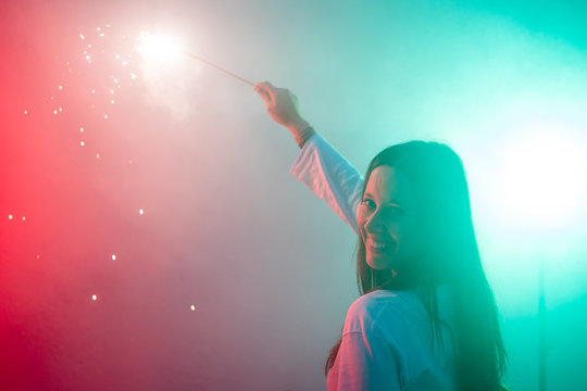 Pretty smiling young woman holding big and colorful sparkler
