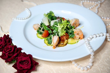 Salad with shrimps and vegetables in a white plate on a vintage tablecloth. Restaurant menu.