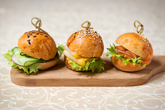 Miniburgers for the buffet on the kitchen board. Restaurant menu.